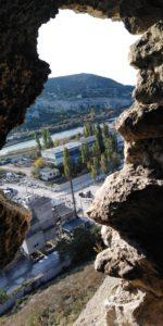 Вид на бетонный завод сквозь проём в пещере